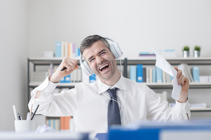 Cheerful businessman sitting at office desk, listening to music using headphones and singing, enjoyment and fun concept